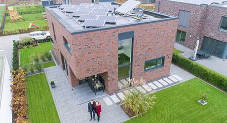 Herr und Frau Thuemler und Ihr EWE Stromspeicher mit einer Solaranlage auf einem Flachdach